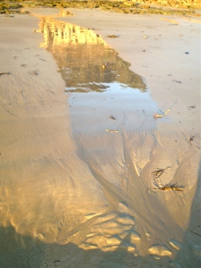 Sand and Reflection photograph with sunrise reflecting on rocks in turn reflected in wet sand.